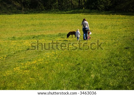 woman walking in a meadow with her child and dog