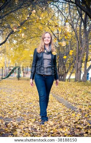woman walking in a park. Autumn season.