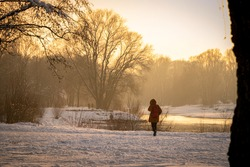woman walking in a winter landscape at sunset with fresh powder snow at the isar, munich, germany