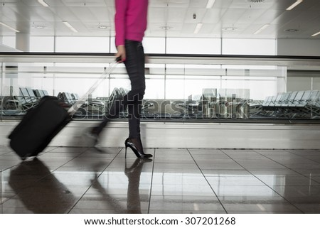 Woman walking in airport, blurred in motion #307201268
