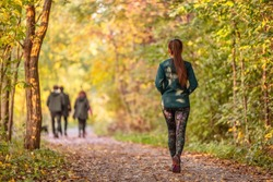 Woman walking in autumn forest nature path walk on trail woods background. Happy girl relaxing on active outdoor activity.