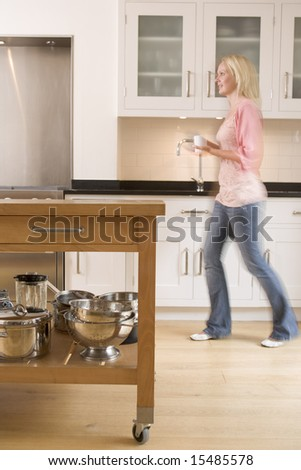 Woman walking in kitchen holding coffee