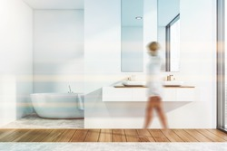 Woman walking in modern bathroom interior with white walls, double sink with mirror and comfortable bathtub in background. Toned image blurred