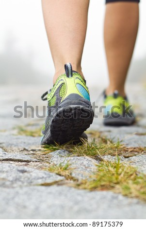 Woman walking in mountains in sport shoes, exercise outdoors