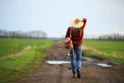 Woman walking in nature, in a rural road, standing back in straw hat, spring, sunset