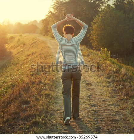 woman walking in nature late afternoon,tinted photo