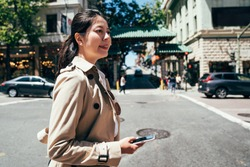 Woman walking in san francisco city using phone app for taxi ride hailing service while commuting from work. Asian office lady sales searching for map visit customer company directions on smartphone.