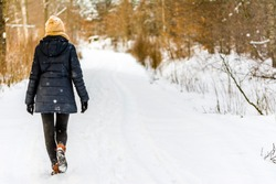 Woman walking in snow in winter clothes. Girl on snowy road in park.