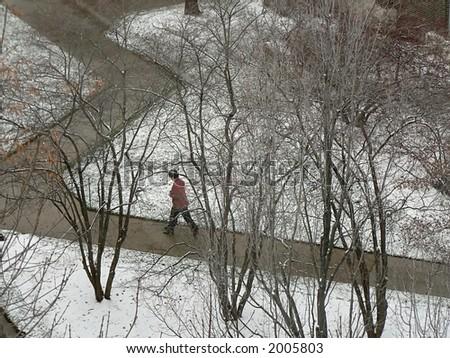 Woman walking in snowy office park.