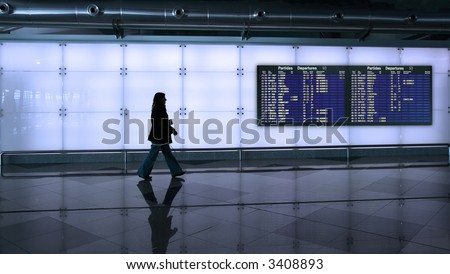 woman walking in the airport with information board
