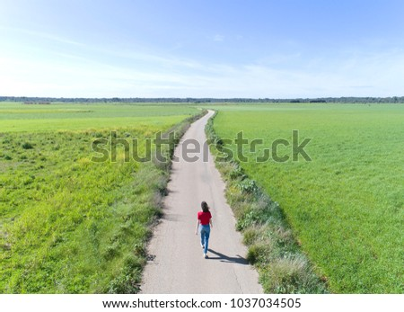 Woman walking in the middle of a lonely road in Mallorca, ses salines, Balearic Islands,  Drone.