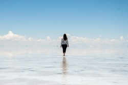woman walking in the salt flats on the mirrored water, celestial sky, heat, mountains and clouds