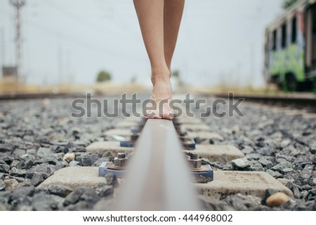 Woman walking in train railway, detail shot of the feets with ba