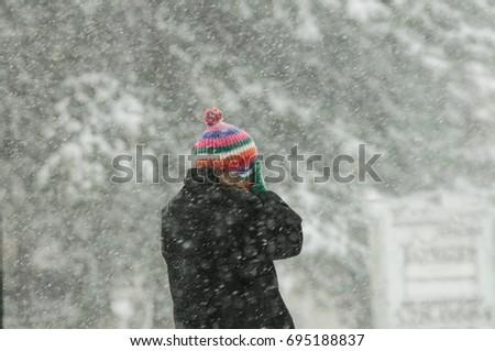 Woman walking in winter blizzard, colourful winter hat