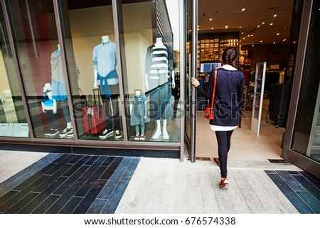 woman walking into a garment store with mannequins
