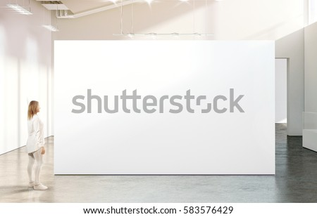 Woman walking near blank white wall mockup in modern gallery. Girl admires a clear big stand mock up in museum with contemporary art exhibitions. Large hall interior, banner exposition