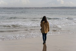 Woman walking on a beach with a yellow jacket in Peniche, Portugal
