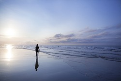 Woman walking on beach at sunrise
