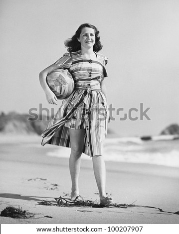 Woman walking on beach carrying ball