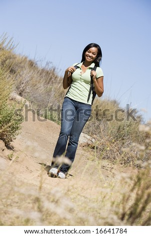 Woman walking on beach path smiling
