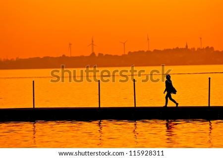 Woman walking on boardwalk with wind turbines in the background at sunset