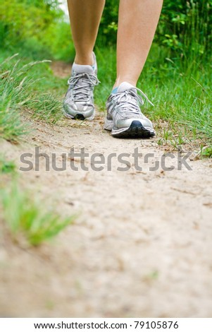 Woman walking on dirt footpath in forest, running and jogging sport shoes