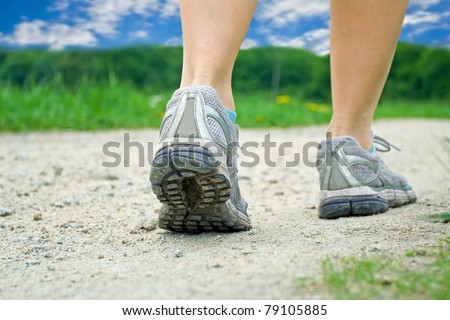 Woman walking on dirt road in summer, running or jogging concept