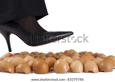 Woman walking on egg shells in high heels, white background.