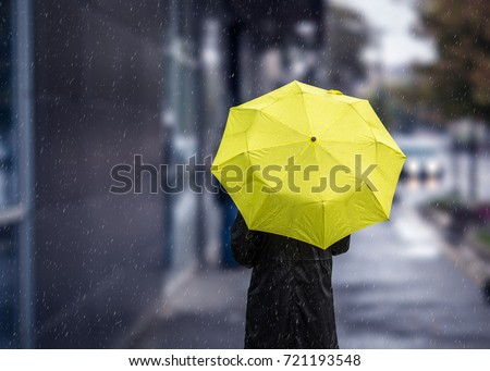 Woman walking on rainy day with yellow umbrella