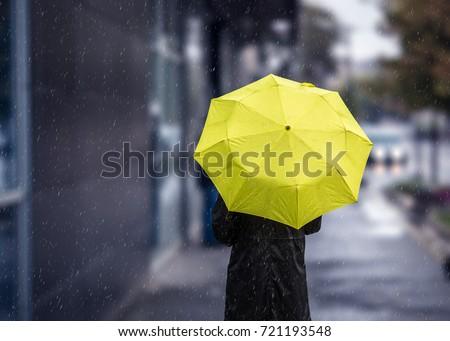 Woman walking on rainy day with yellow umbrella