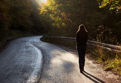 Woman walking on road in autumn afternoon. Beautiful autumn scene.