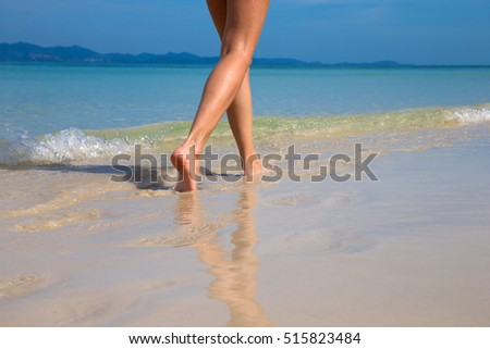 Woman walking on sand beach leaving footprints in the sand #515823484