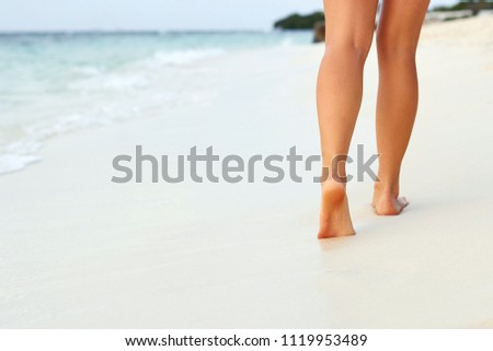 Woman walking on sand beach leaving footprints in the sand. Сlose up of woman leg on the beach.Feet female  #1119953489
