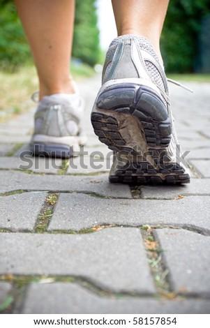 Woman walking on sidewalk, sport shoe close-up