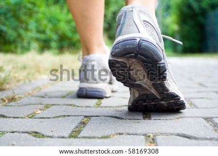 Woman walking on sidewalk, sport shoes closeup