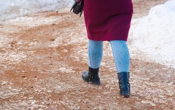 Woman walking on snowy sidewalk spreading with sand, prevention of pedestrians injury. Road service spreading sand on snowy road, sand mixture help increase friction of icy road surfaces in winter