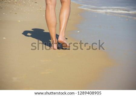 Woman walking on the beach #1289408905