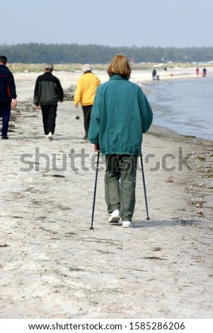 woman walking on the beach with canes