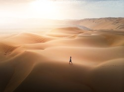Woman walking on the desert sand dunes aerial view at sunset