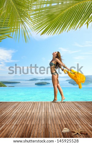 Woman walking on the edge of the swimming pool at luxury summer resort in Greece