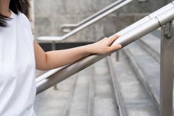 Woman walking on the stair way and grabbing on safety stair rail. Close up shoot on a hand catching a stair rail. Woman aware about safety while walking on the stair way.