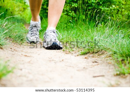 Woman walking on trail path on meadow or forest. Jogging or training outside in summer nature, motivational health and fitness concept.