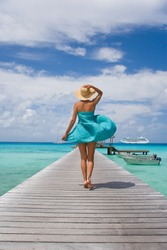 woman walking on tropical cruise ship pier in sarong blowing in wind