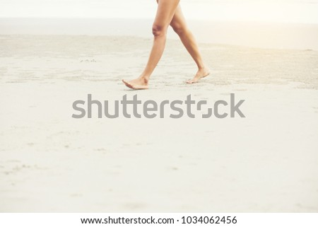 Woman walking on white sand beach in thailand #1034062456