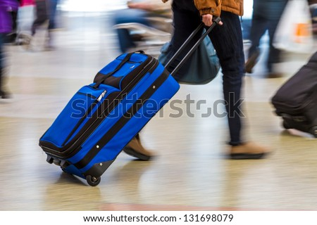 Woman walking quickly pulling blue luggage in busy airport