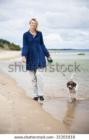 Woman walking the dog on the beach