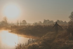 Woman walking through a meadow by a pond in the foggy morning. Sun rising above field and pond flooded with fog in the morning. Real people, authentic situations