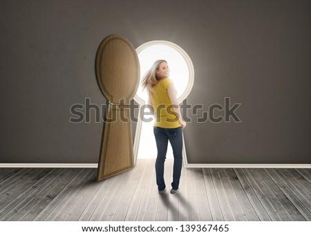 Woman walking towards keyhole shaped doorway with light dark grey room