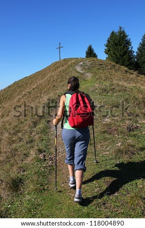 woman walking towards summit cross at the mountain top - stock photo
