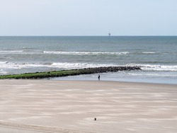 Woman walking waterline near breakwater, beach of North Sea coast of West Frisian island Vlieland, Friesland, Netherlands